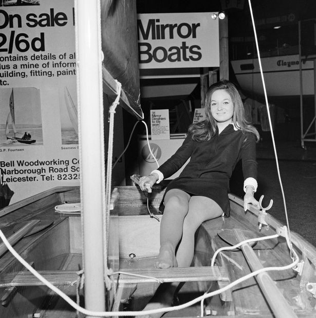 A female model sitting in the stern of a Mirror dinghy with the camera on the bow of the boat