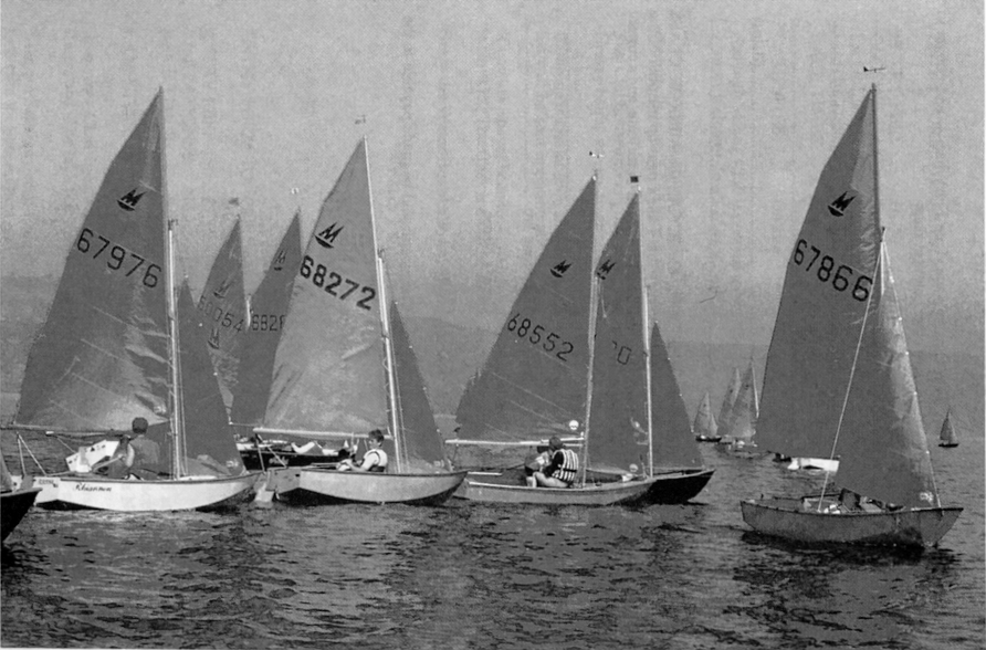A fleet of Mirror dinghies racing to windward in a light wind