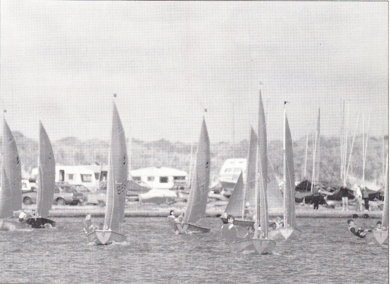 A fleet of Mirror dinghies racing to windward towards the camera in a moderate wind