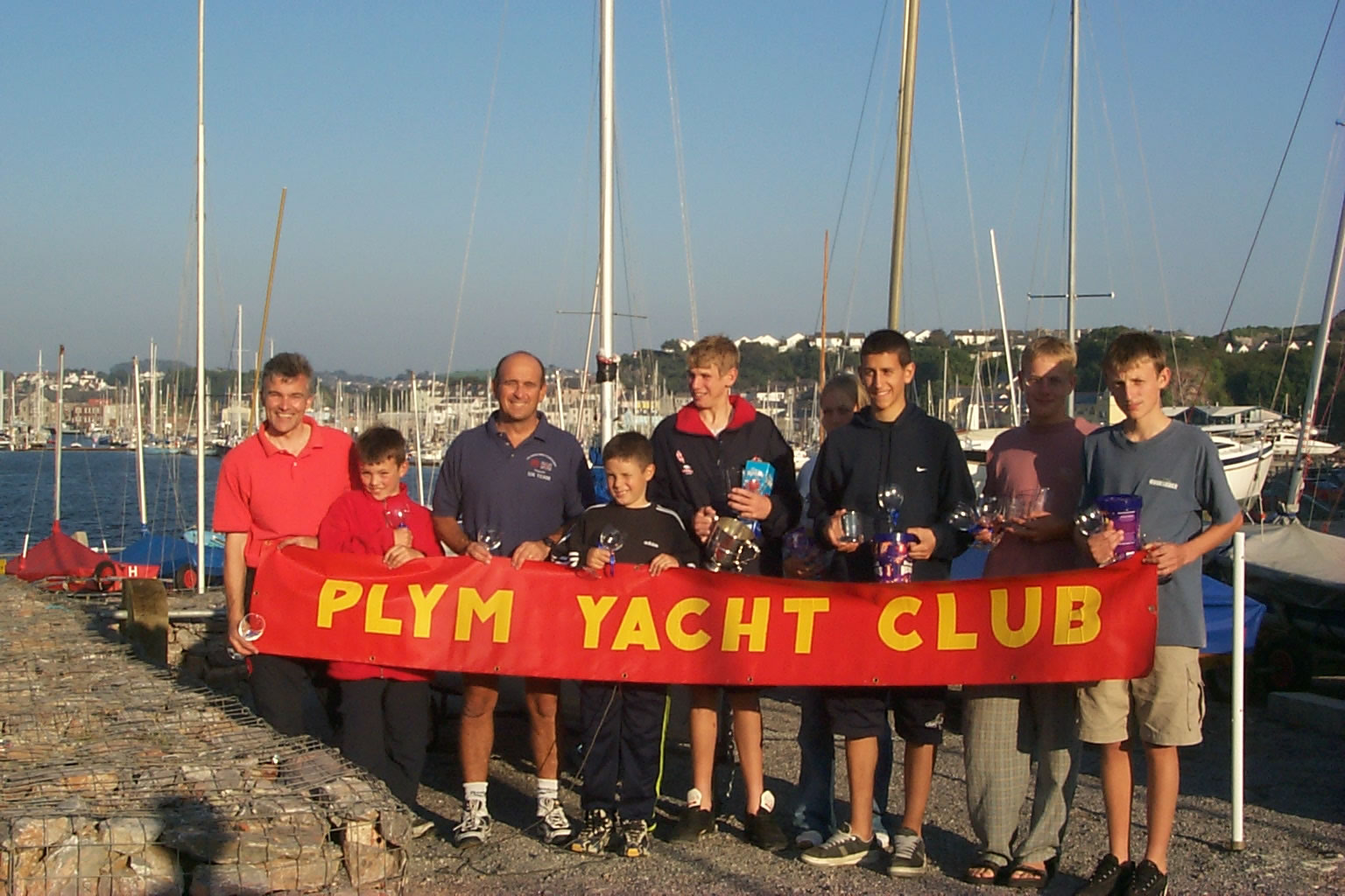 Prizewinning helms and crews behind a red banner with yellow lettering saying 'Plym Yacht Club'