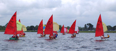 A fleet of Mirror dinghies racing on a run with spinnakers set sailing away from the camera