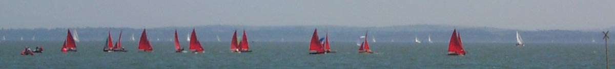 A fleet of Mirror dinghies, rather strung out, in the distance