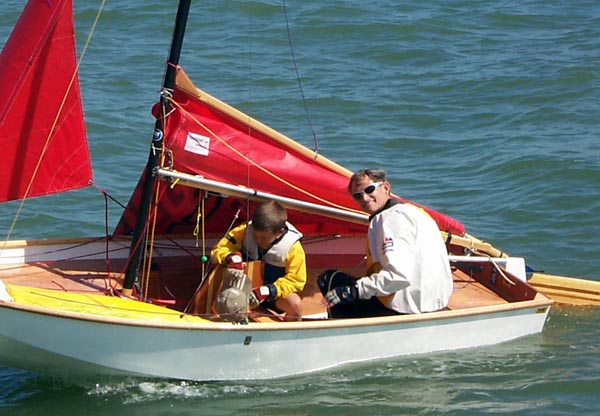 A white GRP composite Mirror dinghy being towed with mainsail down