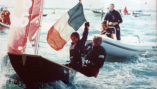 Black Mirror dinghy with crew holding Irish flag after winning World Championship