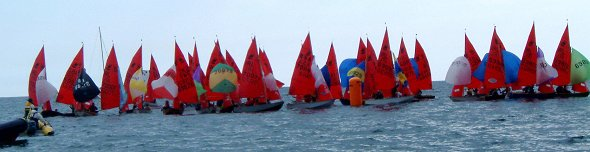 A fleet of Mirror dinghies tightly packed going around the leeward mark in light airs