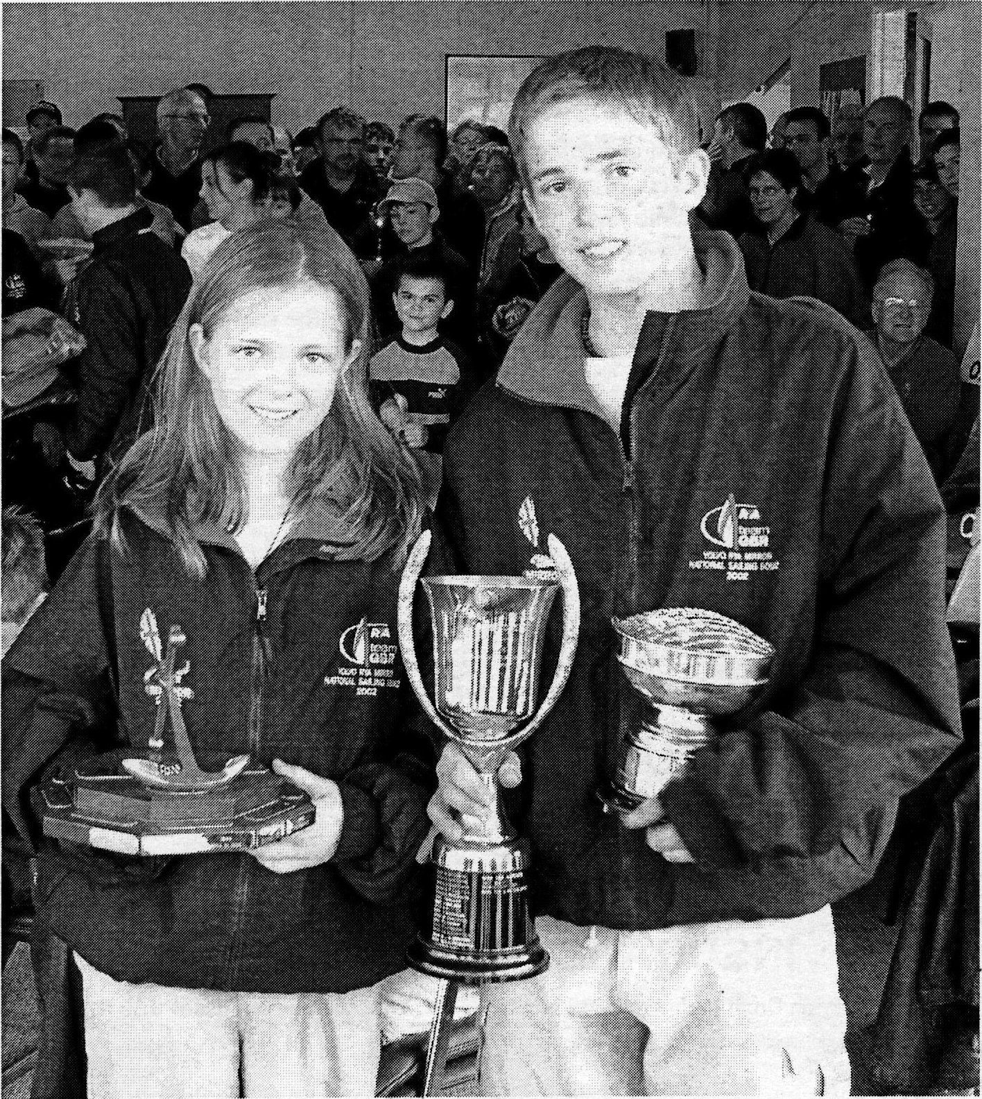 A boy and a girl holding their trophies