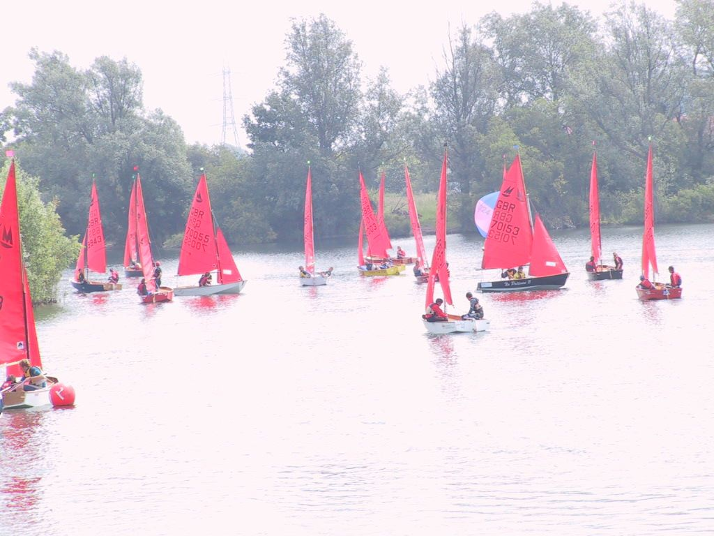 A fleet of Mirror dinghies racing on a small lake