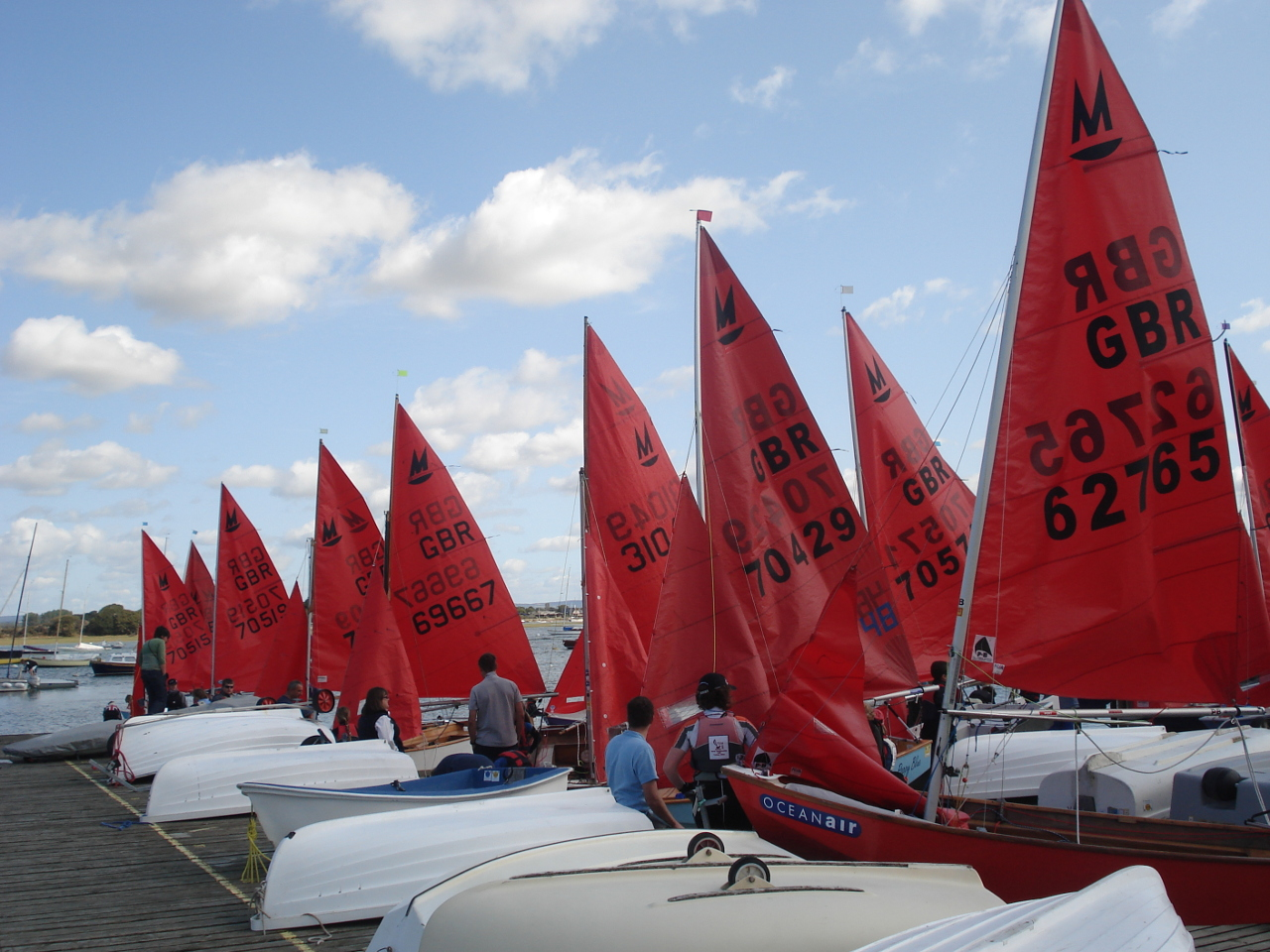 A queue of Mirrors lined up with sails hoisted on the Itchenor SC pontoon waiting to launch
