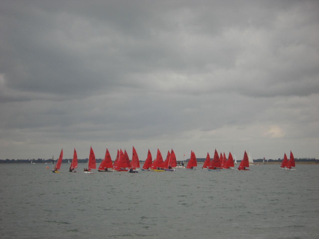 A fleet of Mirror starting a race in the distance under a cloudy sky