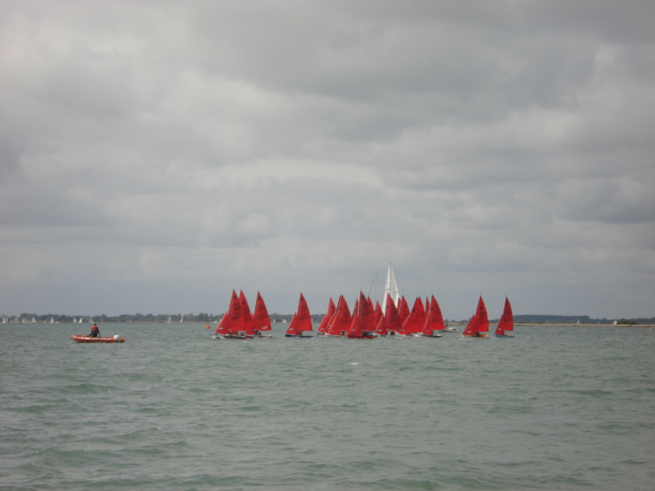 A fleet of Mirror dinghies starting a race in the distance under a cloudy sky