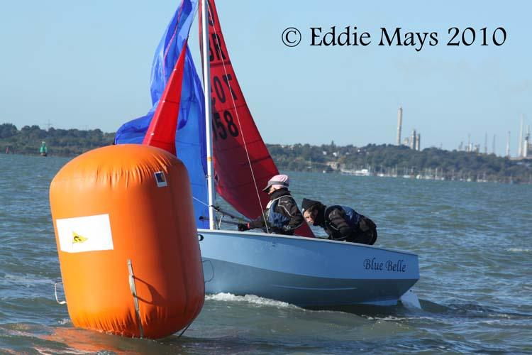 A blue Mirror dinghy dropping her spinnaker with the large orange inflatable leeward mark in the foreground