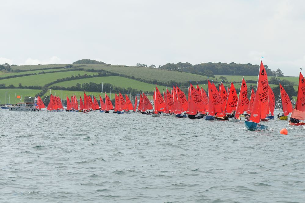 A fleet of Mirrors lining up to start with the Committee boat in the distance and some green rolling hills of Cornwall in the background