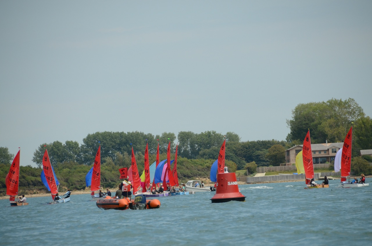 A fleet of Mirrors racing downwind with a red can buoy in the foreground
