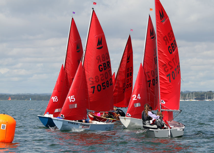 A fleet of Mirror dinghies racing with the windward mark in the background and boats with spinnaker flying sailing towards the camera