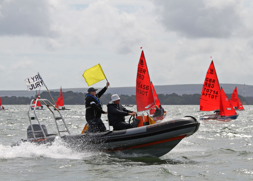 A Jury RIB at speed with jury member waving yellow flag