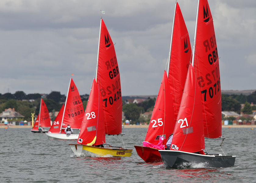 Mirror dinghies closely bunched racing to windward with beach huts in the background