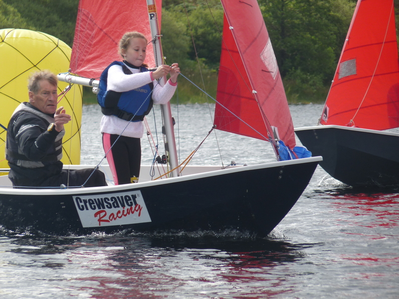 A Mirror dinghy rounding the windward mark with crew standing up cliping guy into pole end