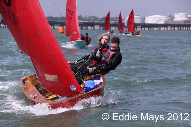 A red Mirror dinghy sailing to windward in a chop