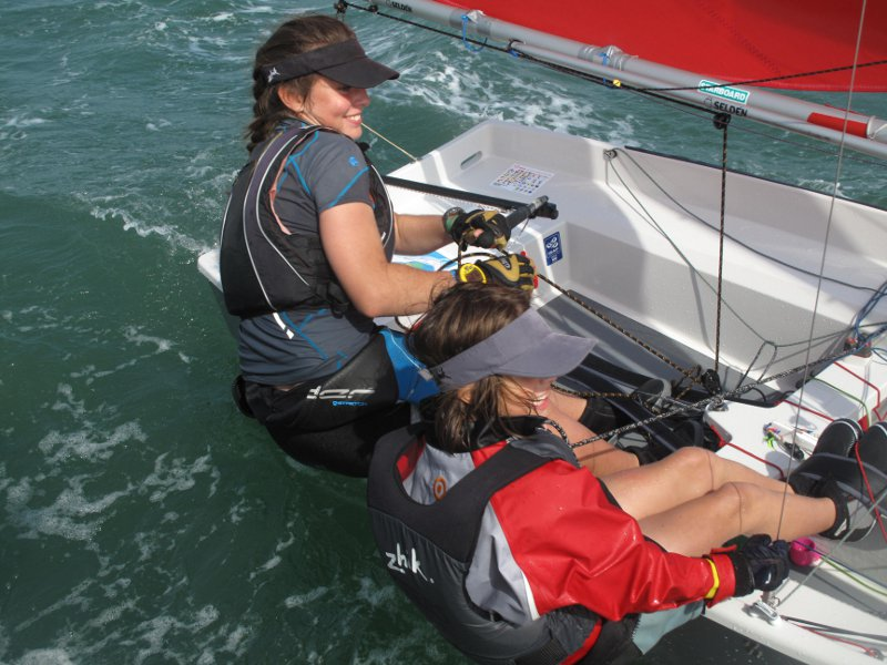 Two girls sailing a grey GRP Mirror to windward viewed from the committee boat
