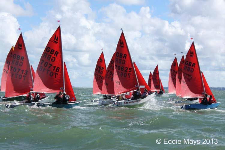 A fleet of Mirror dinghies sailing to windward just after the start of a race
