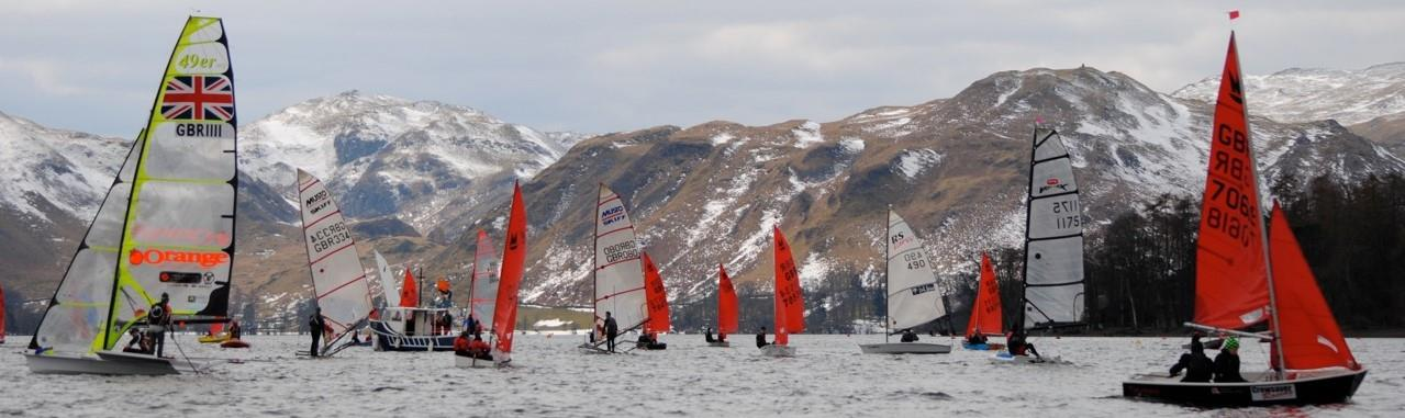 Boats getting ready for a start with snow on the hills in the background