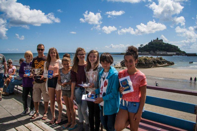 prize winners on a sunny balcony with St Michael's Mount in the background