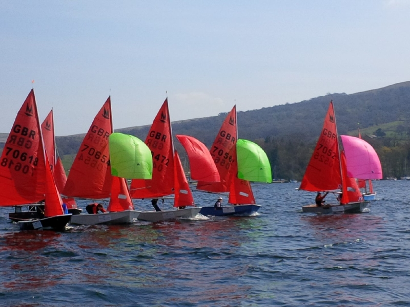 A fleet of Mirrors racing on a lake with spinnakes set