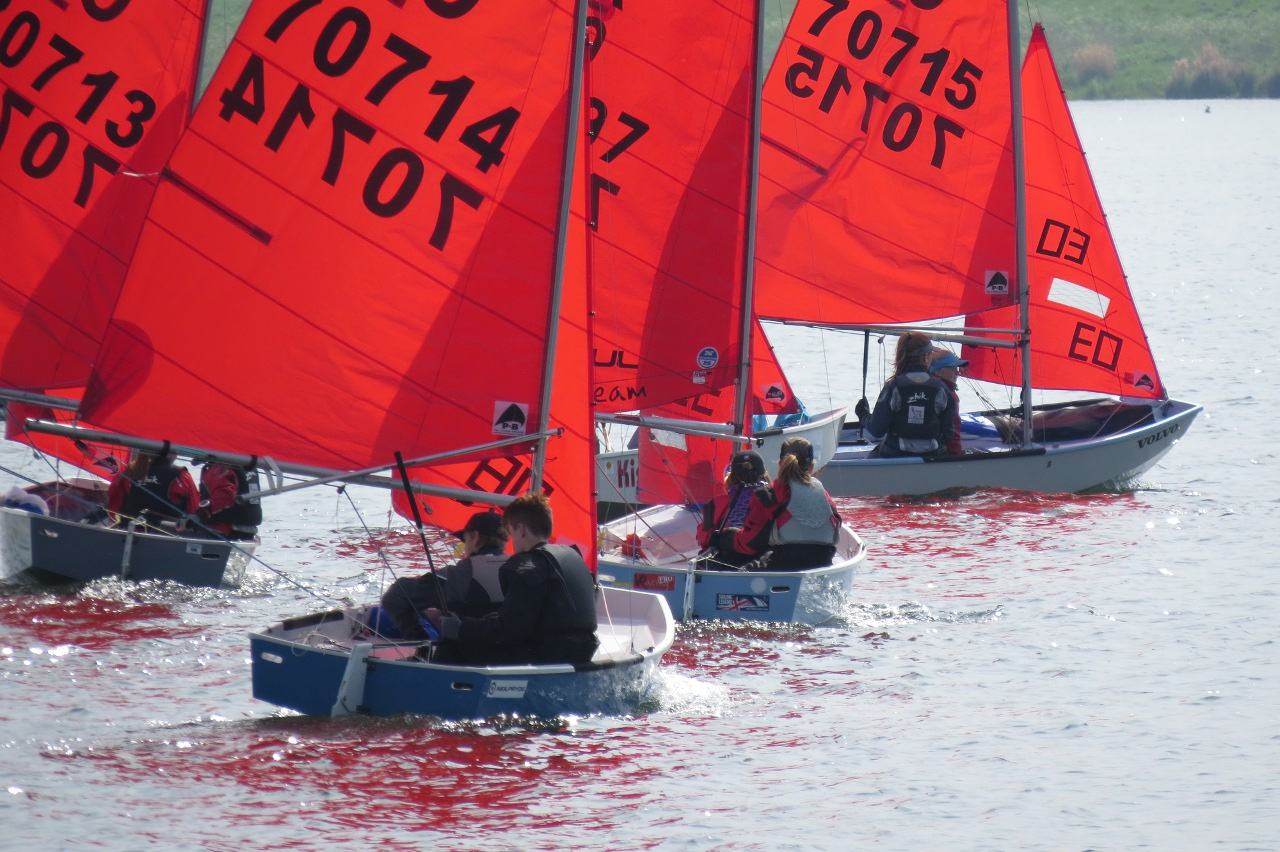 Mirror dinghies on starboard tack on a lake in a light wind