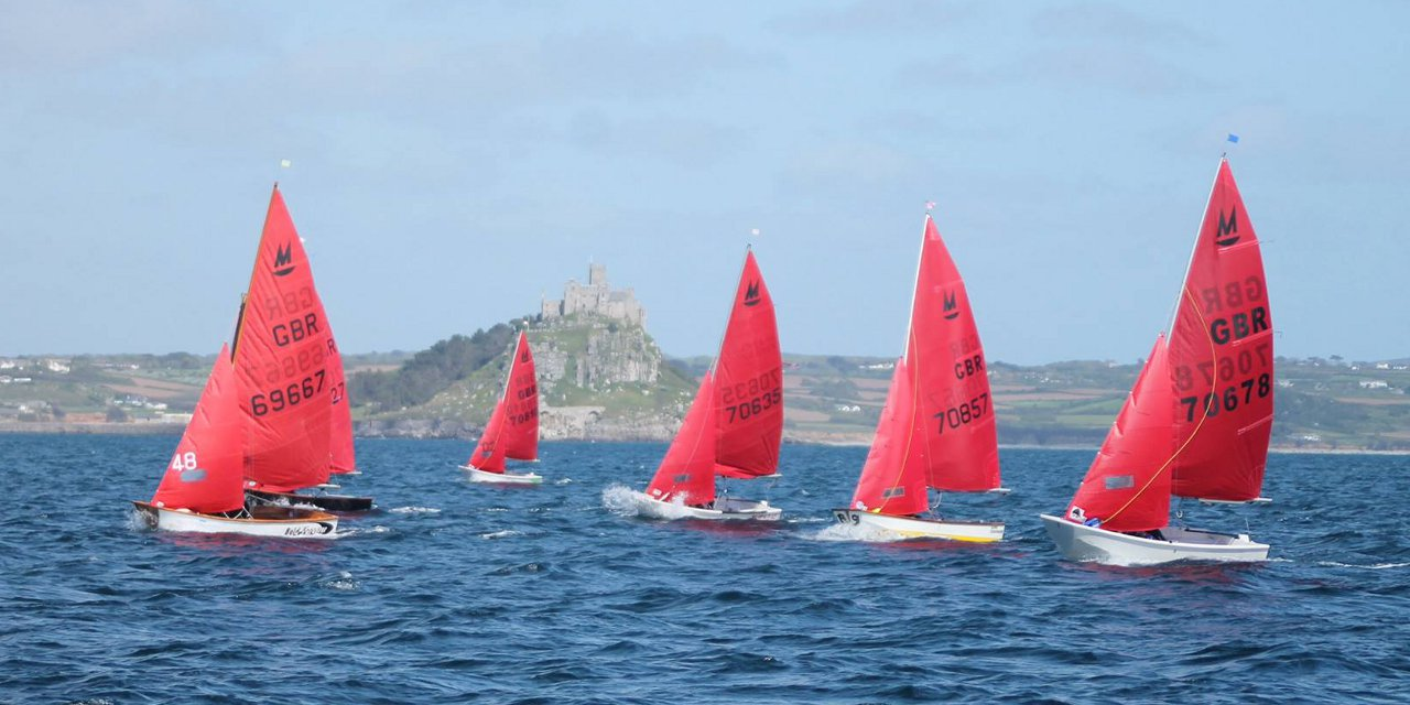 A fleet of Mirrors just after the start of a race with St Michael's Mount in the background