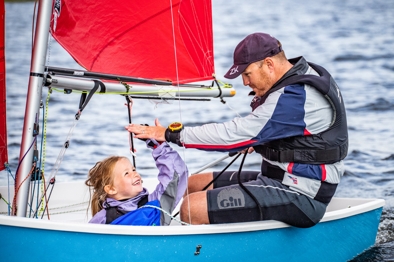 Father and daughter high fiving in a blue Mirror dinghy