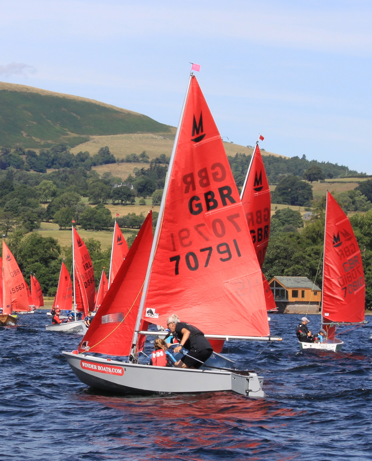 A grey GRP Mirror dinghy manouvering before a race start