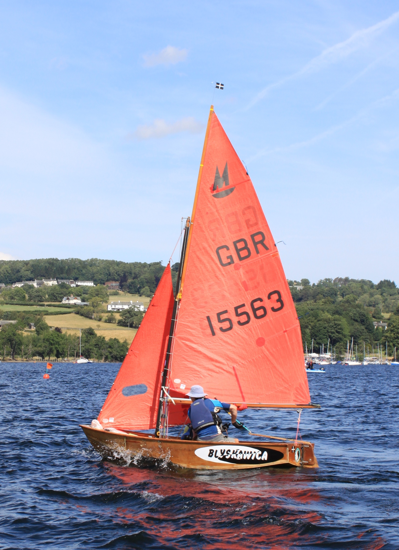 A varnished wooden Mirror dinghy with gaff rig racing to windward on Ullswater in the Lake District