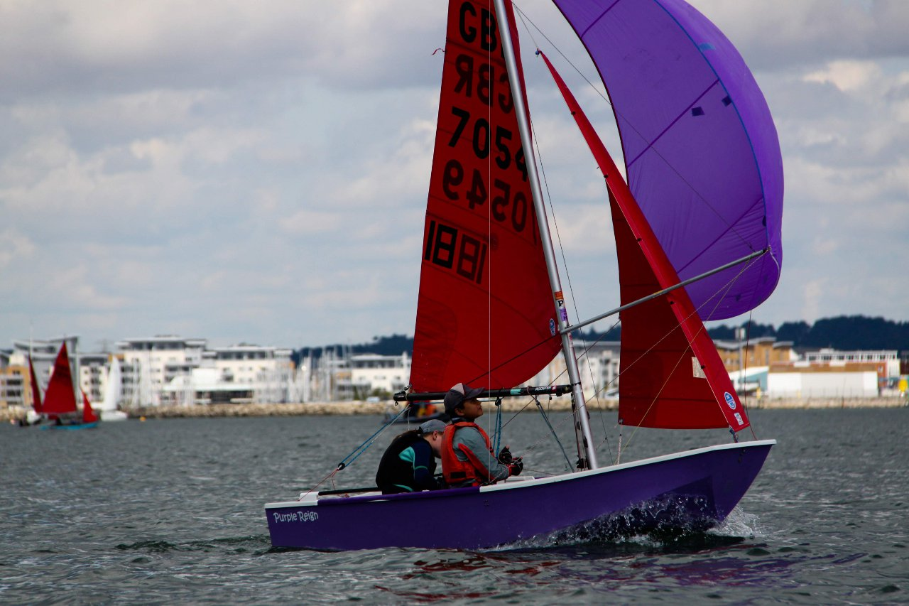 A purple Mirror with purple spinnaker sailing across the picture under a gloomy sky