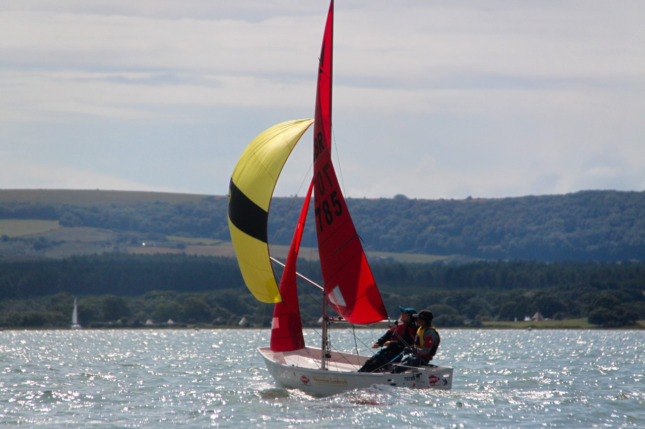 A white Mirror with yellow and black striped spinnaker sailing away from the camera
