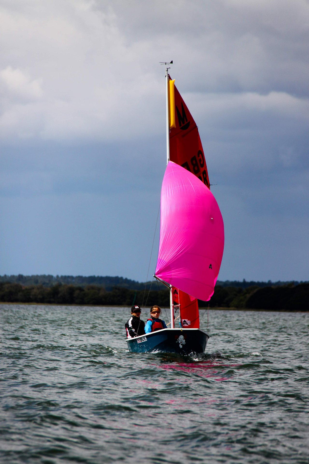 A Mirror racing with spinnaker set sailing towards the camera