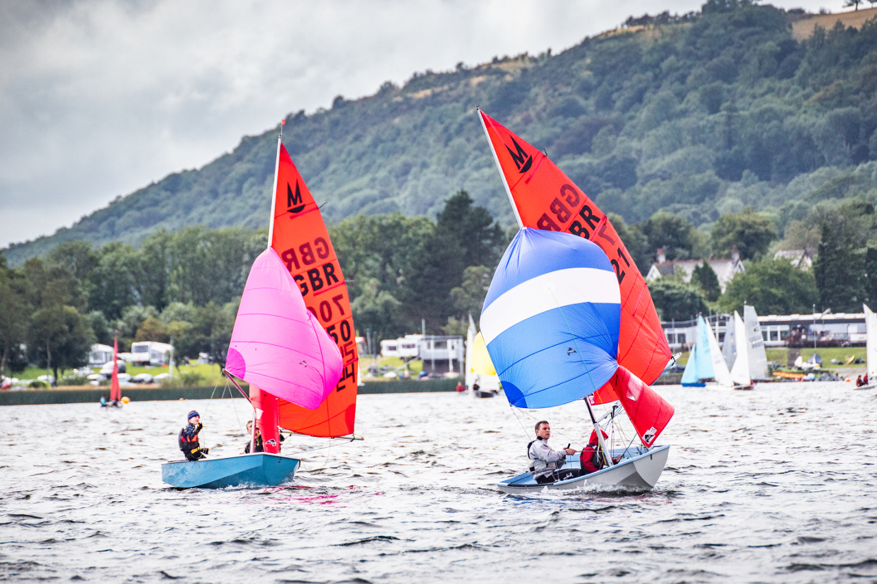 Two Mirror dinghies racing close together with spinnakers set with a sailing club, other boats, in the distance and the hills of the lake district in the background