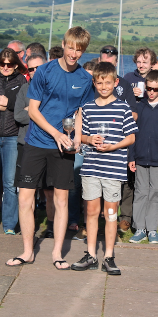 An older teenager and younger boy receive their prizes