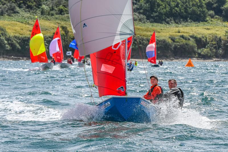 A blue GRP Mirror dinghy racing with spinnaker towards the camera sailed by a father and daughter