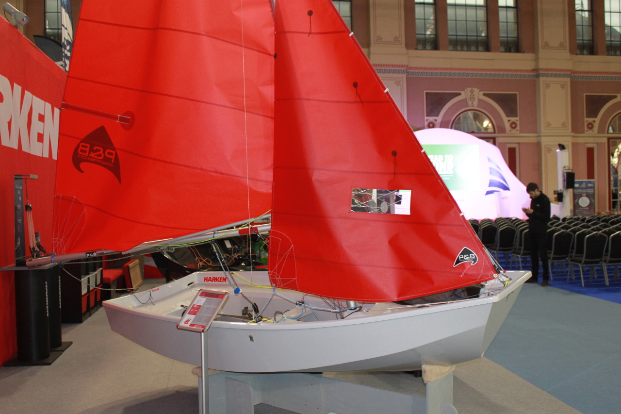 A white GRP Mirror dinghy at the RYA Dinghy Show viewed side on with the Main Hall stage in the background