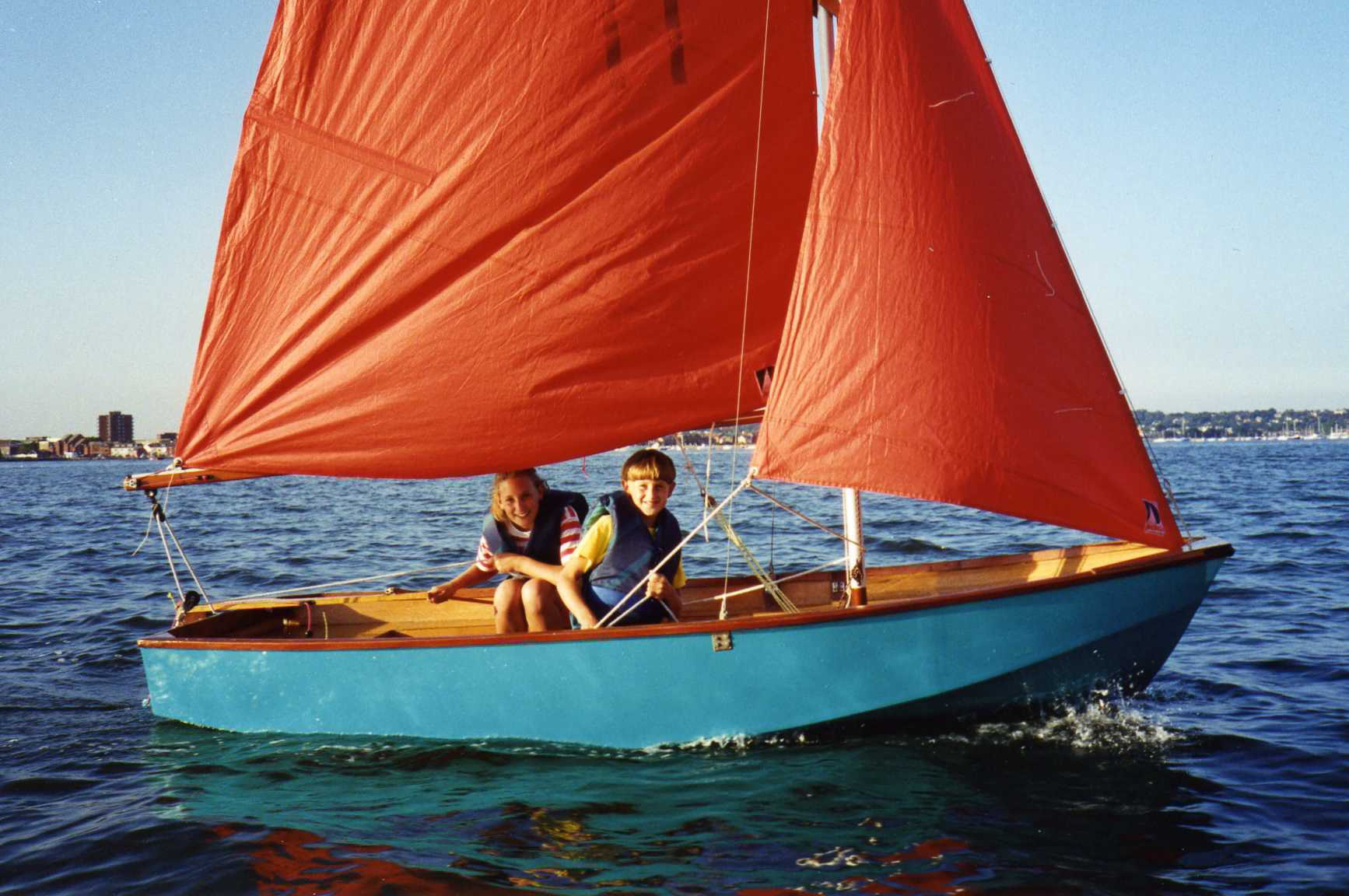 Light blue wooden Mirror dinghy, number 11, sailing on a sunny day