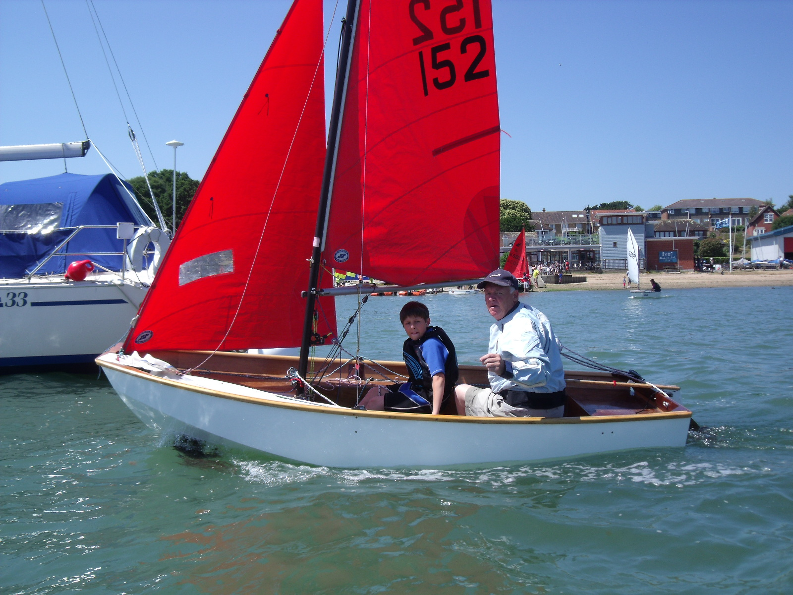 A very old, but buitifully restored Mirror dinghy sailing on a sunny day with a moored yacht in the background