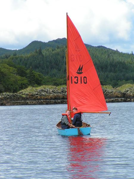 An old blue wooden Mirror dinghy being sailed in a light wind
