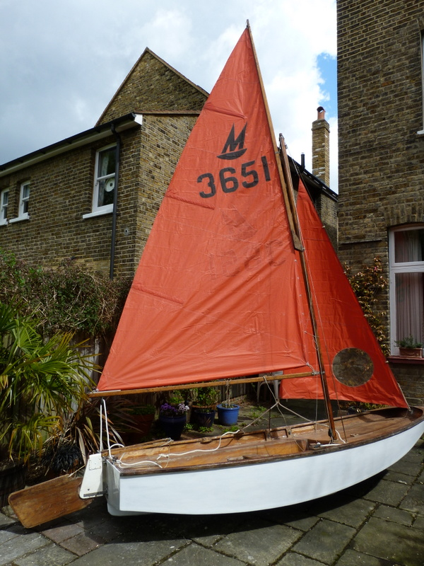 White wooden Mirror dinghy in a paved garden with sails hoisted
