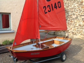 A red wooden Mirror dinghy rigged, with sails up, on a driveway