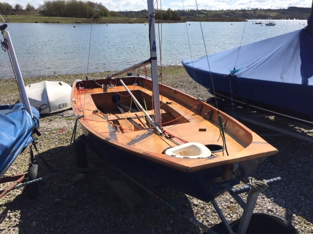 A wooden Mirror dinghy with cover off, mast up, but no sails, by  a lake