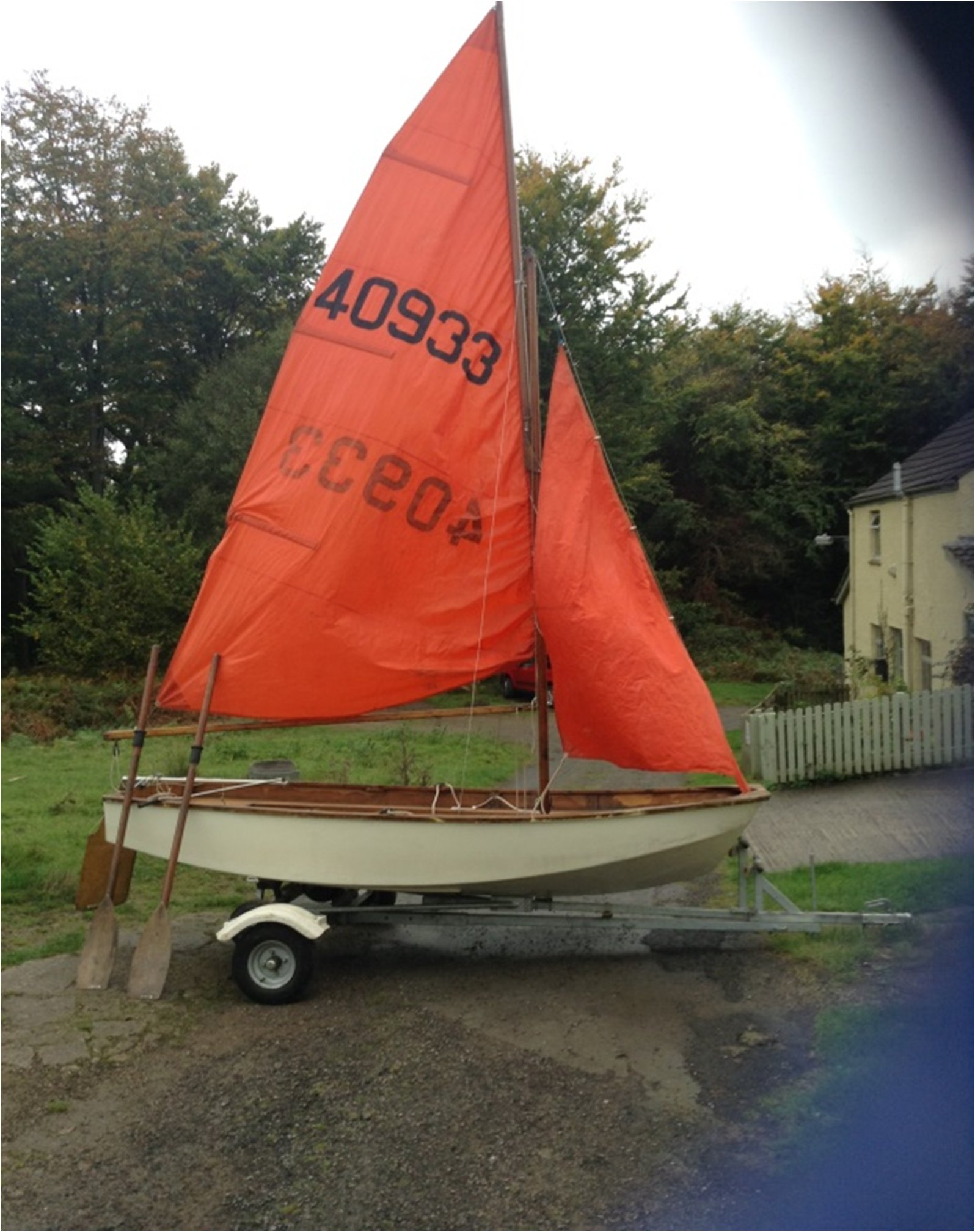 A white wooden Mirror dinghy rigged up on a combination trailer/trolley