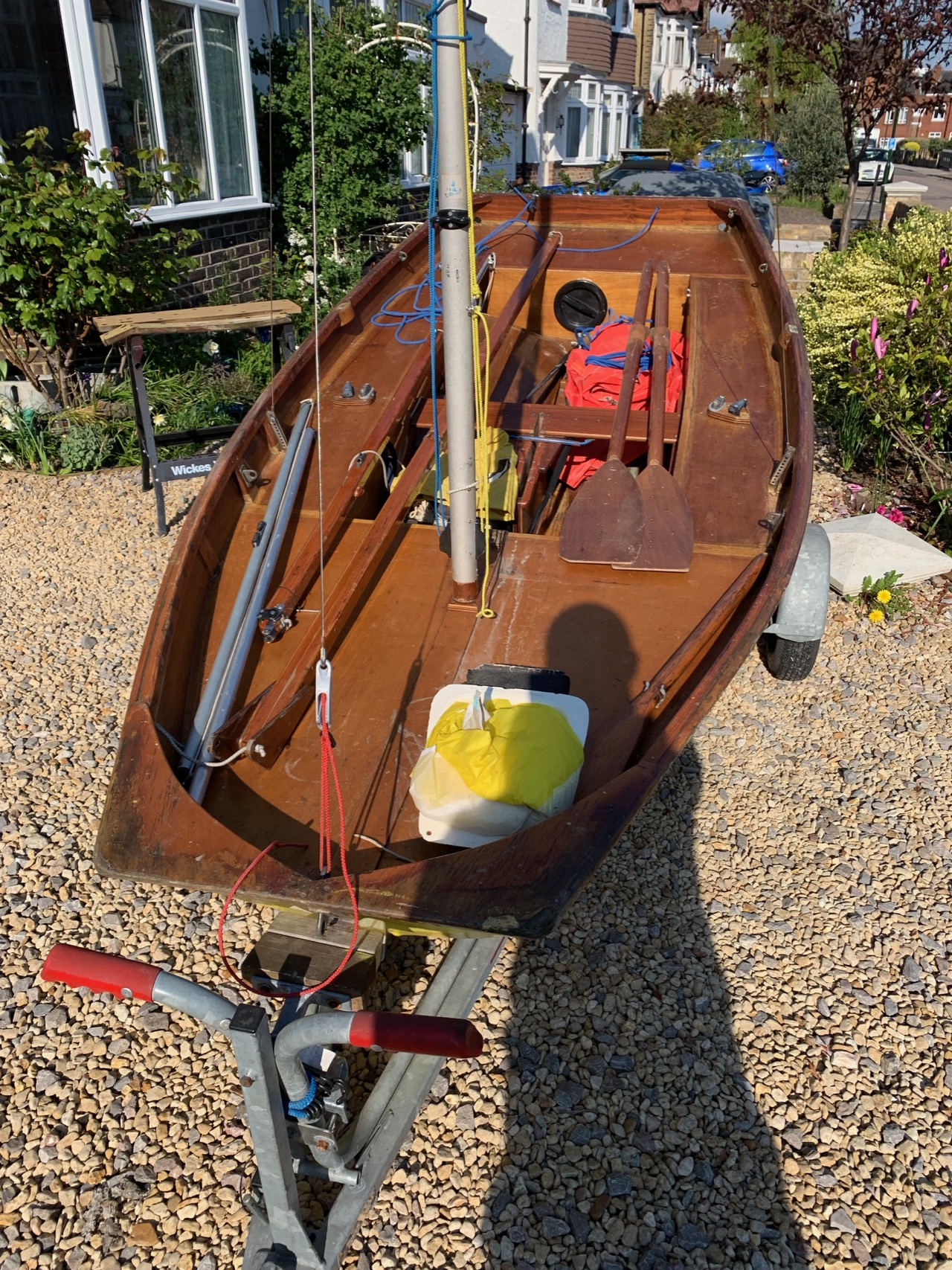 A yellow wooden Mirror dinghy with mast up on a driveway