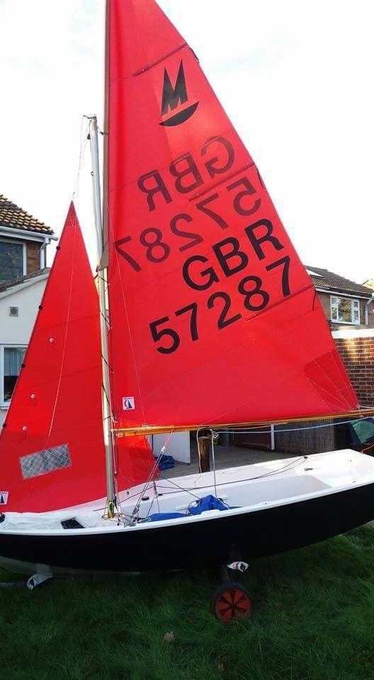 Black Mirror dinghy, with white interior and lovely looking sails rigged on on a front garden