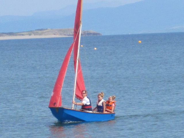 A blue Mirror dinghy being sailed by father and two daughers