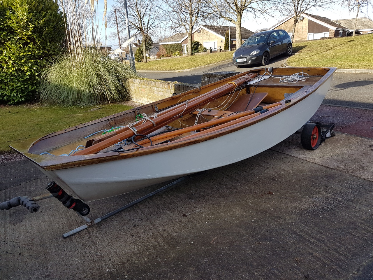A whilte wooden Mirror dinghy unrigged on a driveway